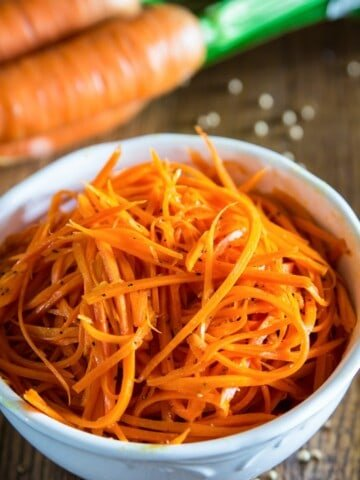 shredded carrot salad in a white bowl with coriander sprinkled next to it