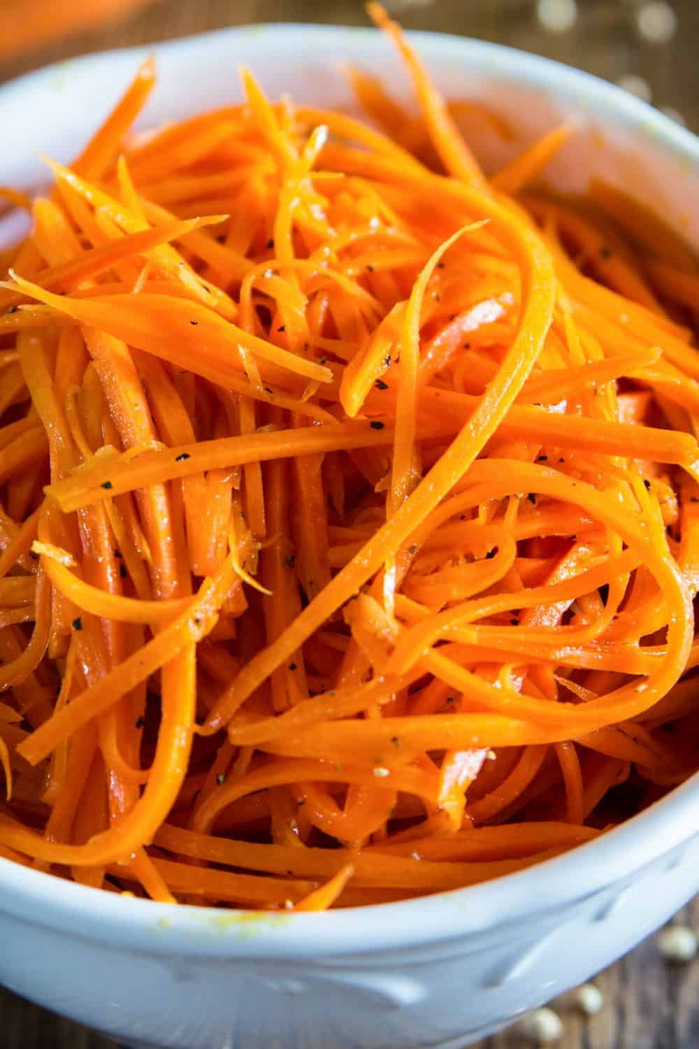 shredded carrot salad in a white bowl with black pepper on top