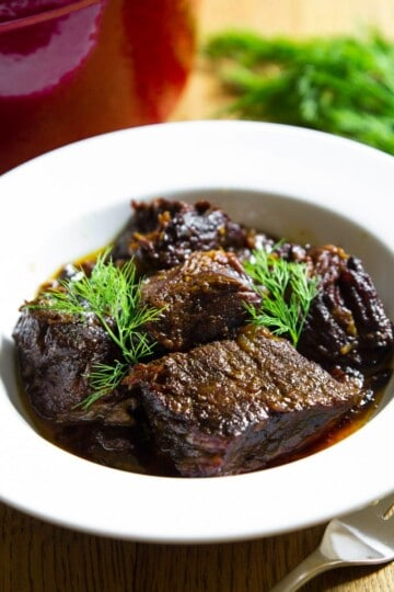 braised beef in a white bowl with fresh dill on top