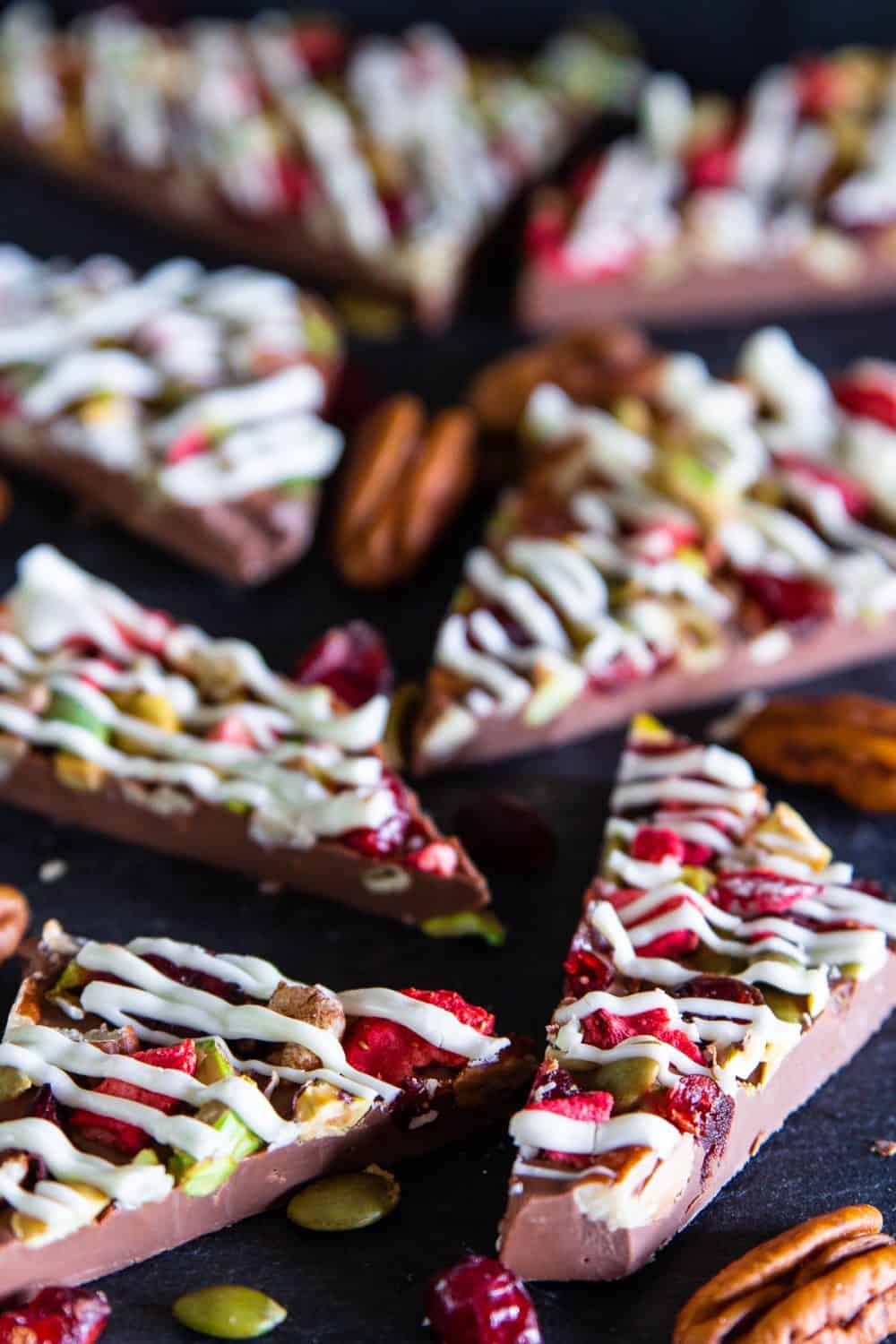 Up close picture of large pieces of chocolate bark with dried fruits and nuts and drizzled on top with white chocolate laying on a dark surface