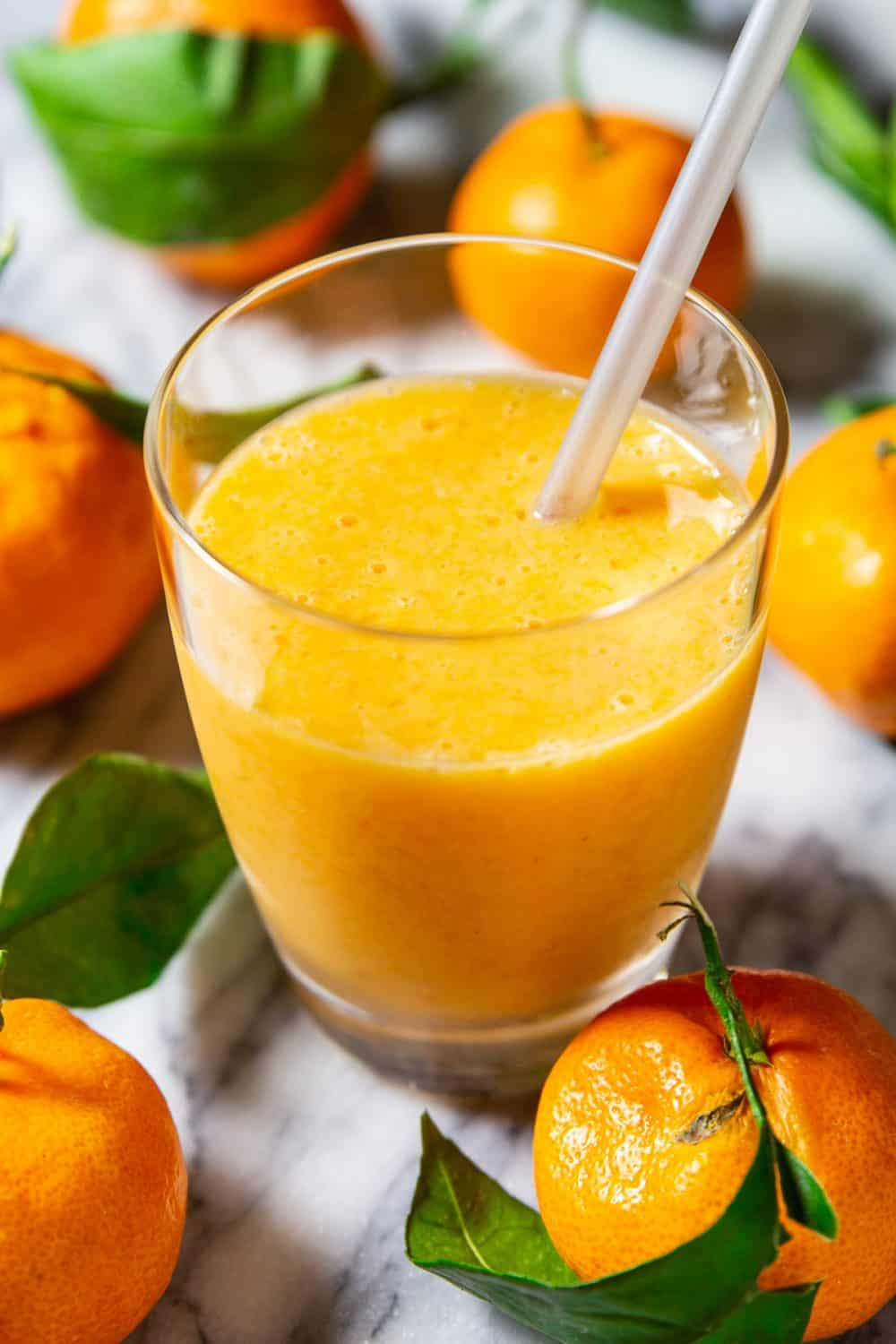 Up close image of mandarin and banana smoothie recipe in a small glass with straw on a marble counter surrounded by fresh manadarins