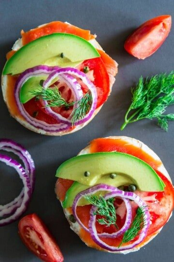 smoked salmon bagel with cream cheese, avocado, tomato, capers, and red onion