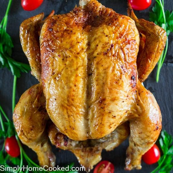 Roasted chicken with cherry tomatoes and parsley around the chicken