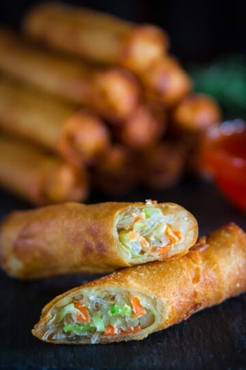 fried spring rolls sliced in half with a glass bowl full of sweet chili sauce next to it.