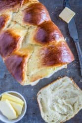 brioche bread loaf with a slice of brioche bread and sliced butter beside it