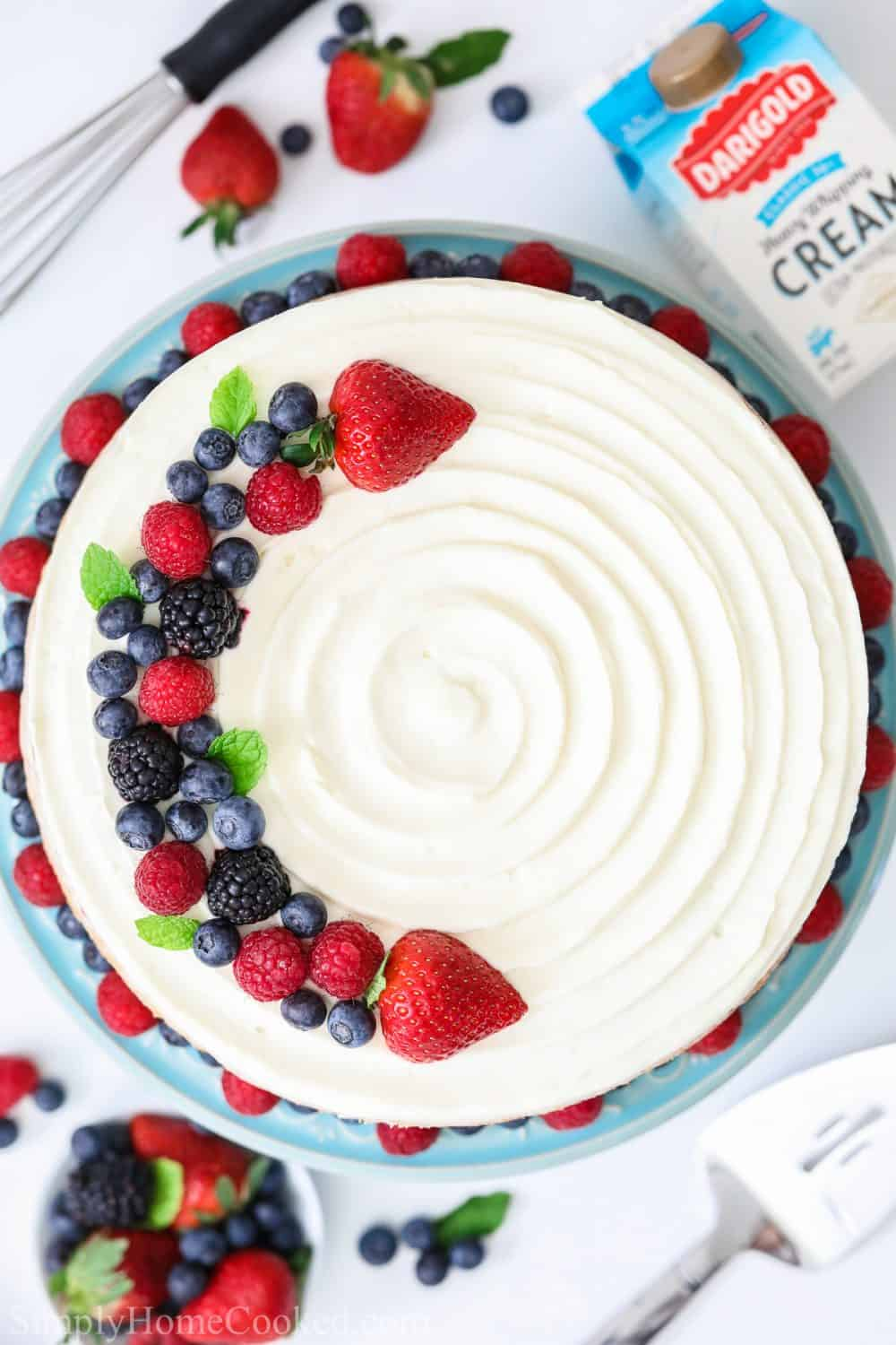 overhead shot of a white Chantilly cake with berries on top