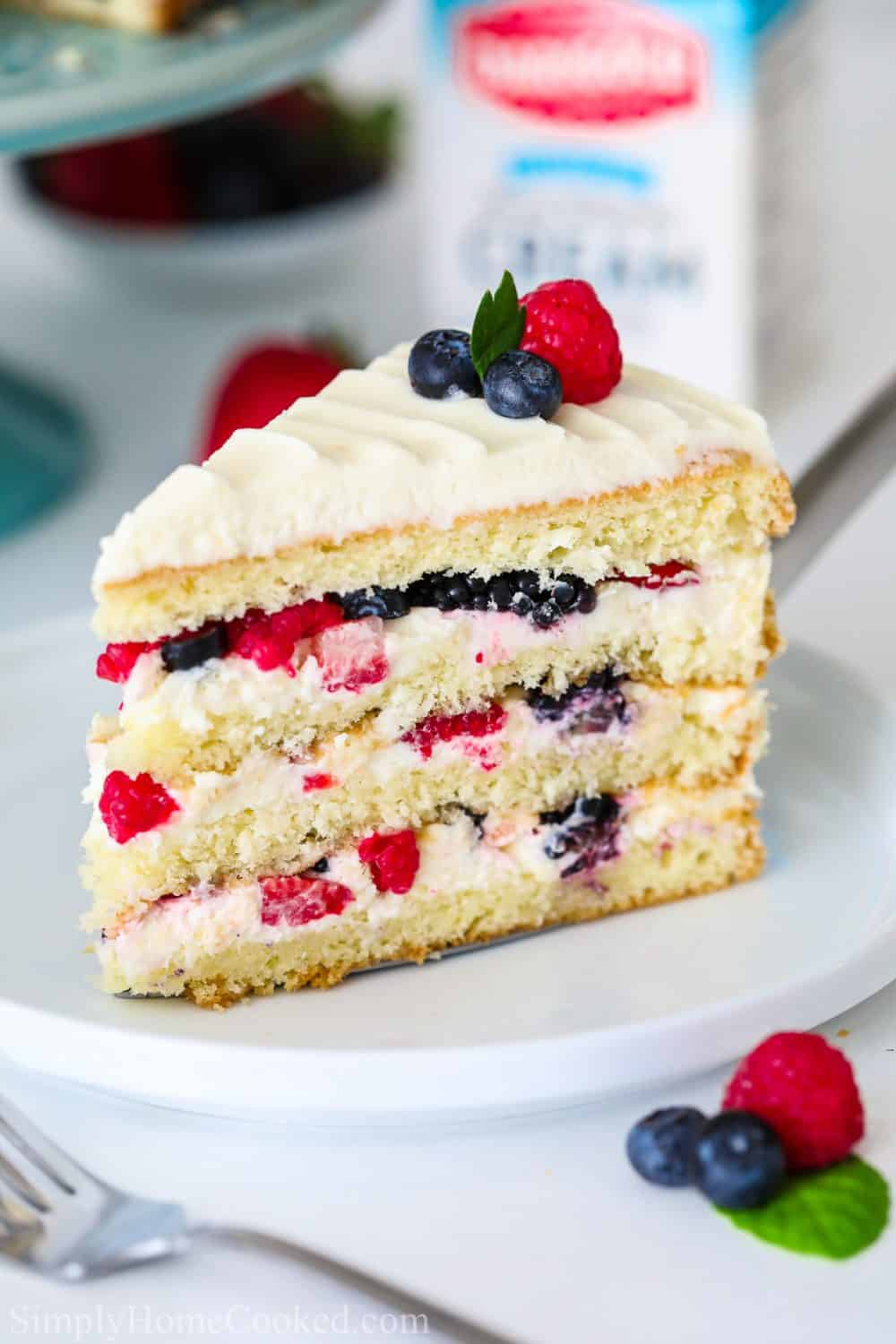sliced Chantilly cake with berries on top on a white plate with a blue cake stand behind it