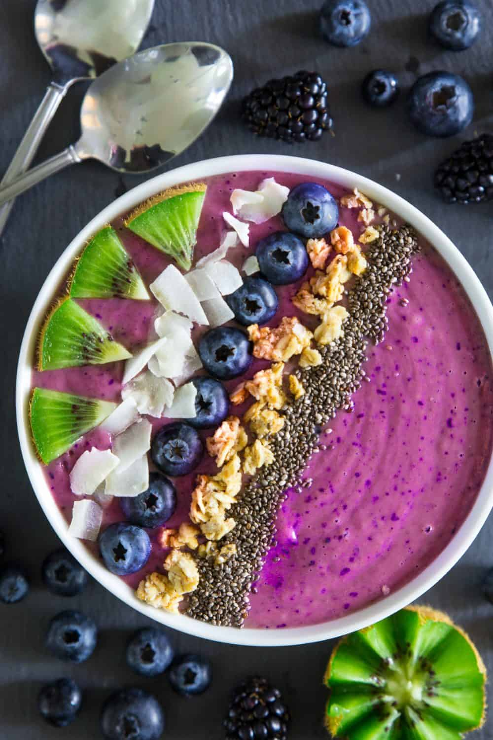 blueberry smoothie bowl with chopped kiwi, coconut flakes, granola, and chia seeds on top