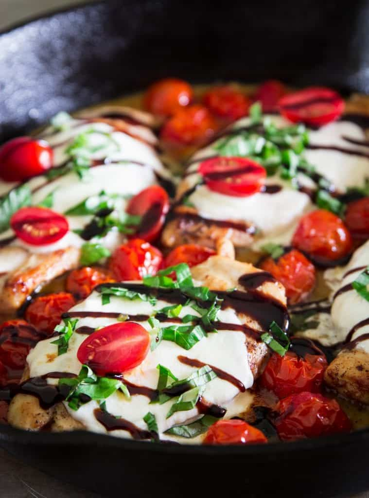 cooked chicken breast in a cast iron pan with mozzarella cheese, cherry, tomatoes, basil, and balsamic vinegar on top
