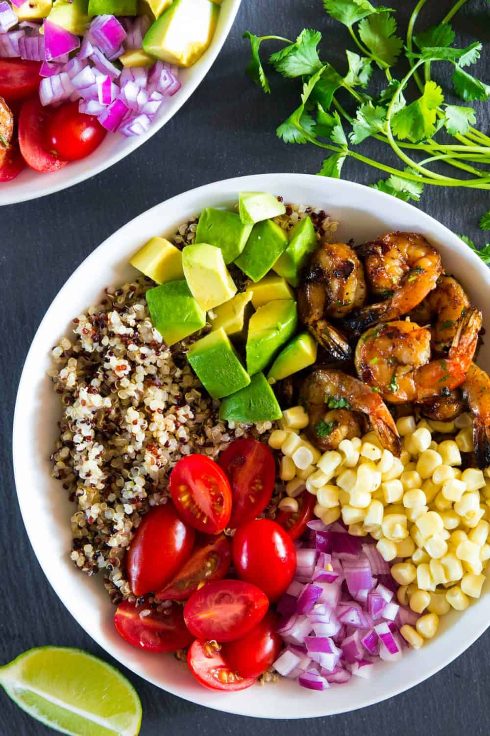 Overhead picture of a white bowl on a black surface filled with quinoa, shrimp, corn, onion, tomato, and avocado making this shrimp quinoa bowl with a fresh cilantro dressing