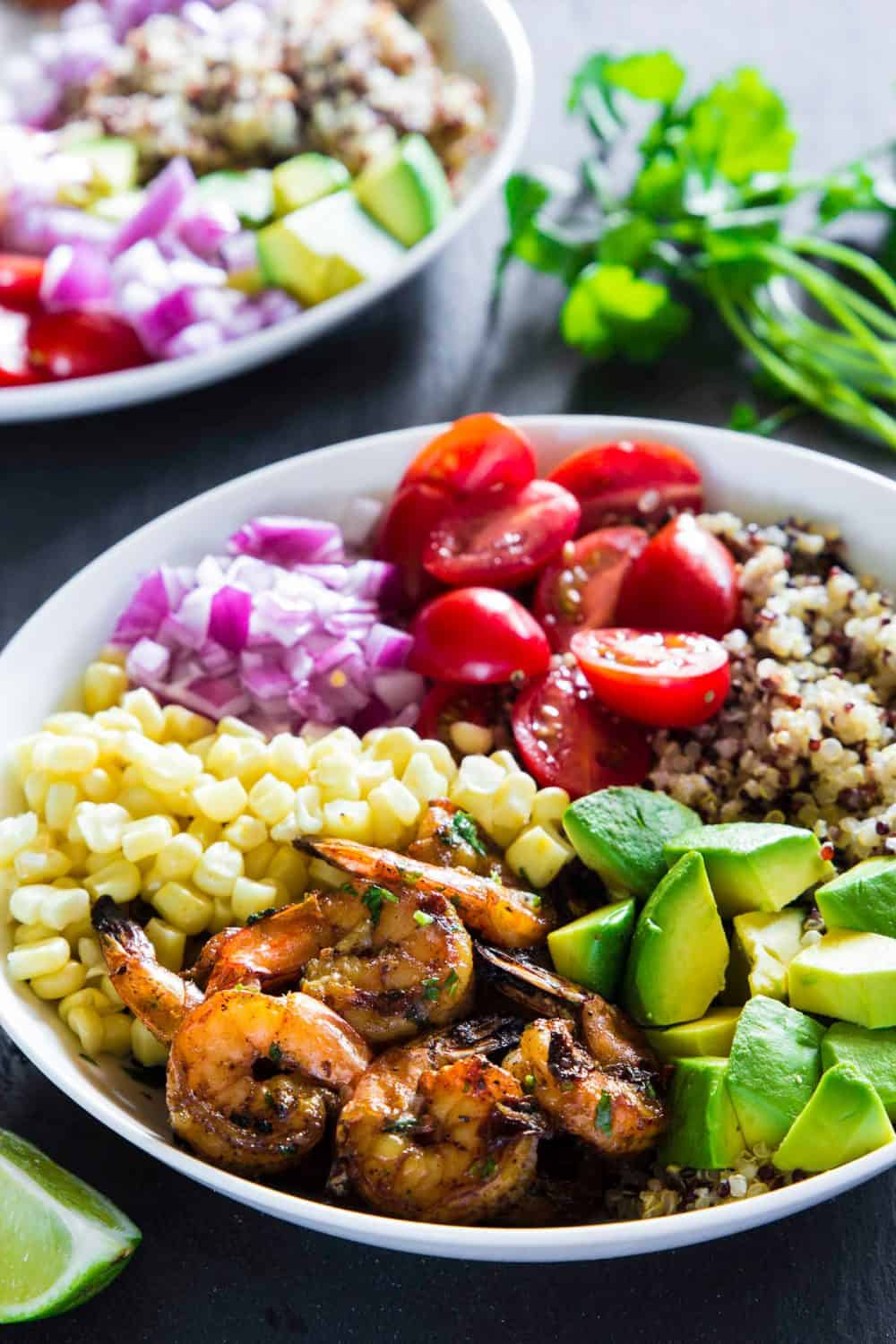Large white bowl filled with quinoa, shrimp, corn, onions, tomatoes, and avocado to create a Shrimp Quinoa Bowl sitting on a dark wooden surface