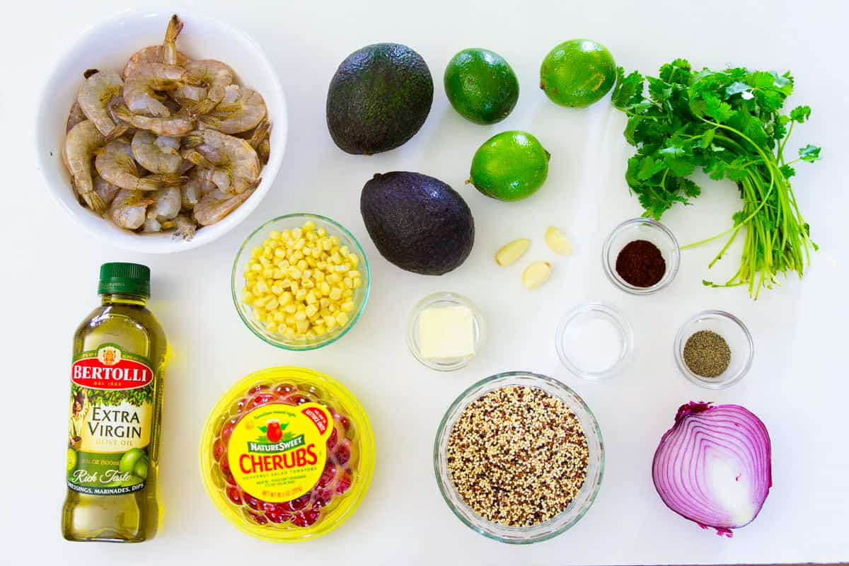 Ingredients for shrimp quinoa bowls laying on a flat white surface