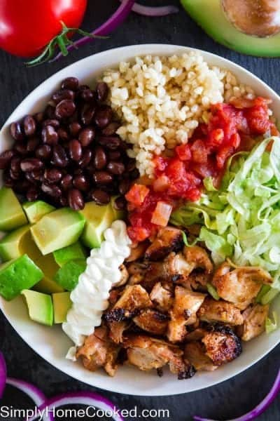 chipotle chicken bowl with chicken, avocado, lettuce, salsa, sour cream, black beans, and brown rice
