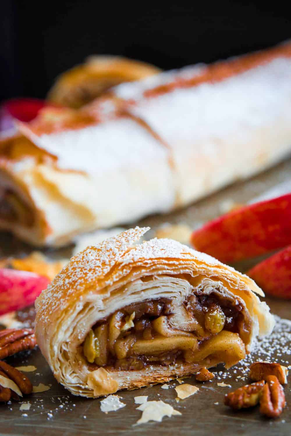 Apple strudel on a flat brown surface with a close up shot of a slice showing flaky crust and layers of cooked apples and pecans with a dusting of powdered sugar on top