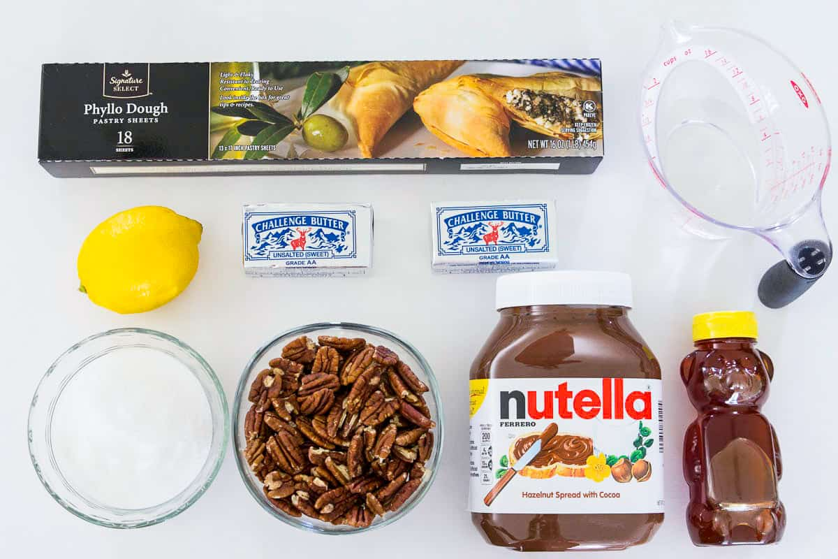 Ingredients for baklava recipe with nutella laying on a flat white surface and photographed from overhead
