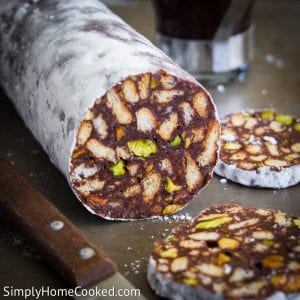 a roll of Chocolate Salami with 2 slices cut on the side. part of a knife seen next to the chocolate salami