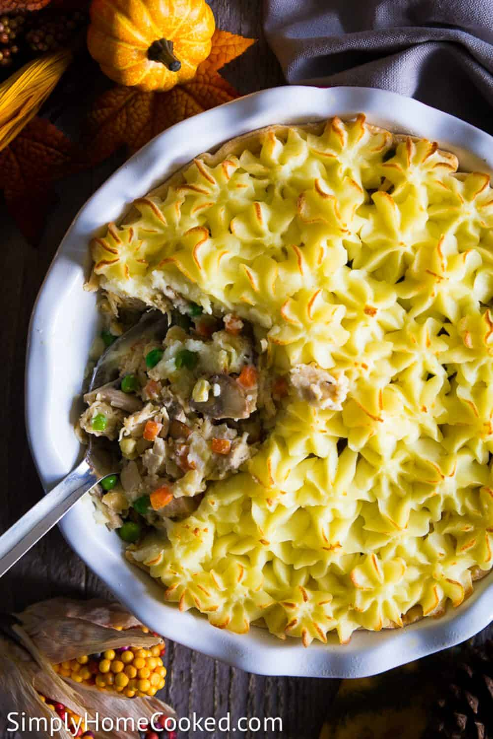 An overhead image of a leftoveer turkey shephers pie with a large spoon in the center and a small pumpkin above it