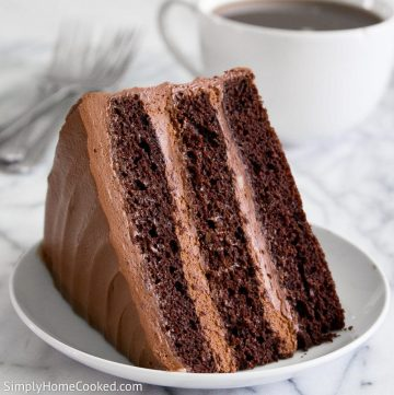 Nutella Fudge Cake slice on a white plate with a cup of coffee behind the cake