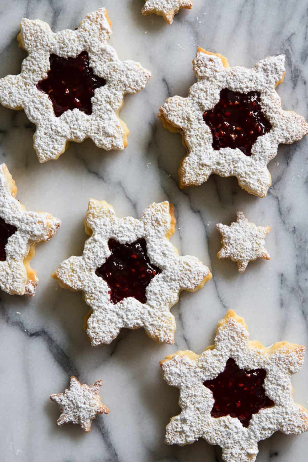 Close up of snowflake-shaped linzer cookies with raspberry jam and topped with powdered sugar on a white marbled background.