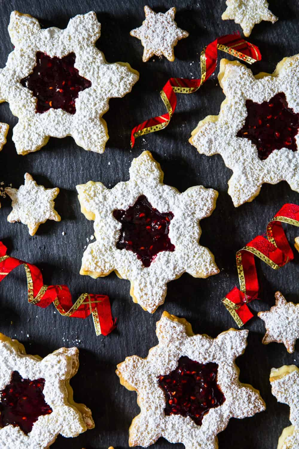 Raspberry jam linzer cookies shaped like snowflakes and dusted in powdered sugar, 3 large and 3 small, along with 3 curling red Christmas ribbons