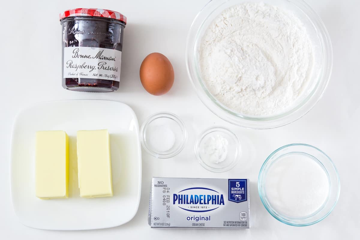 Ingredients for Linzer cookies with Raspberry jam: jar of raspberry jam, egg, bowl of flour, bowl of sugar, 2 sticks of butter, Philadelphia cream cheese, baking powder, and salt.