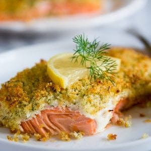 panko crusted salmon with a slice of lemon on a white plate with fresh dill on top.