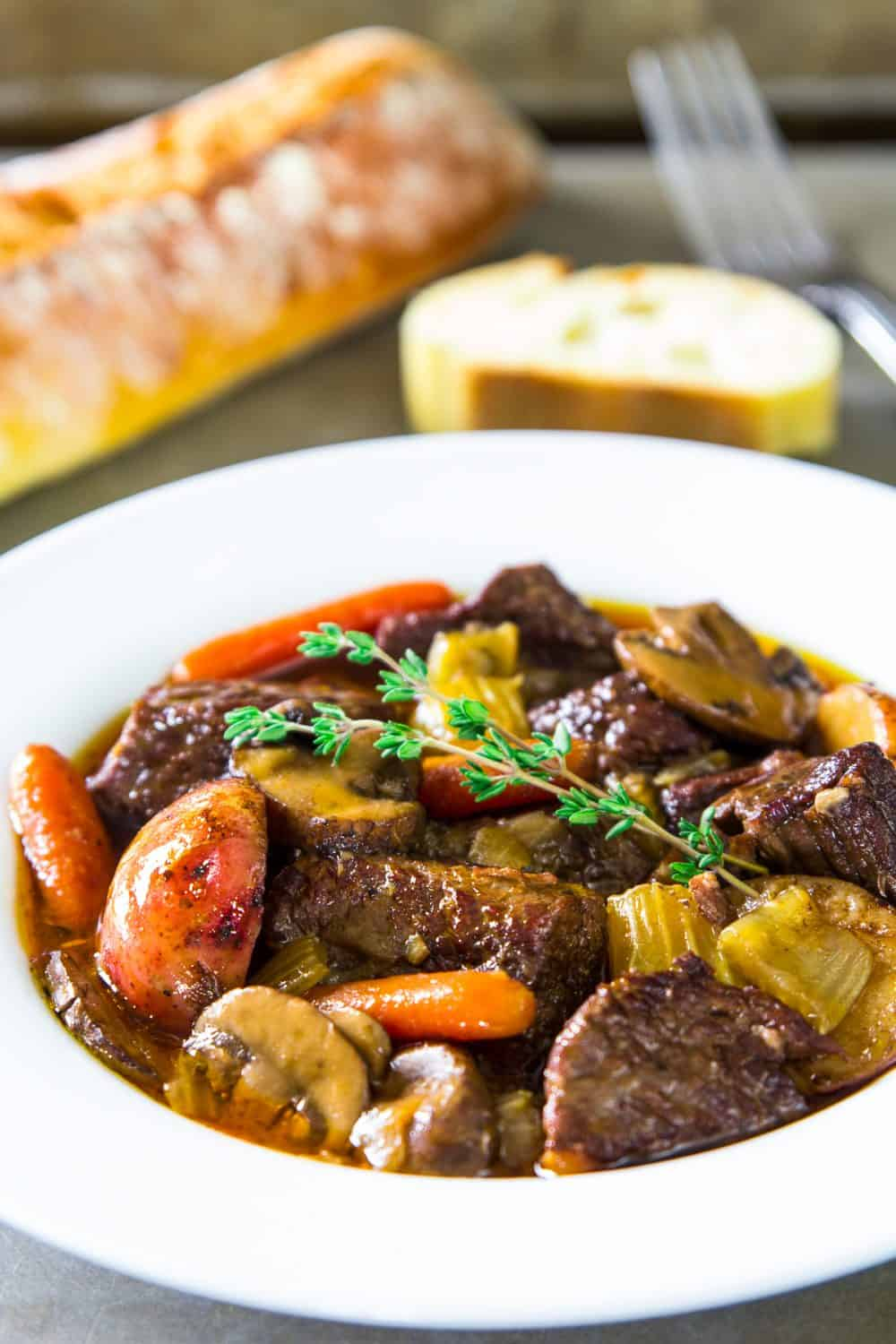 beef stew in a white bowl with fresh thyme on top and french bread beside it