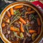 braised beef stew in a red dutch oven pot with herbs beside it.