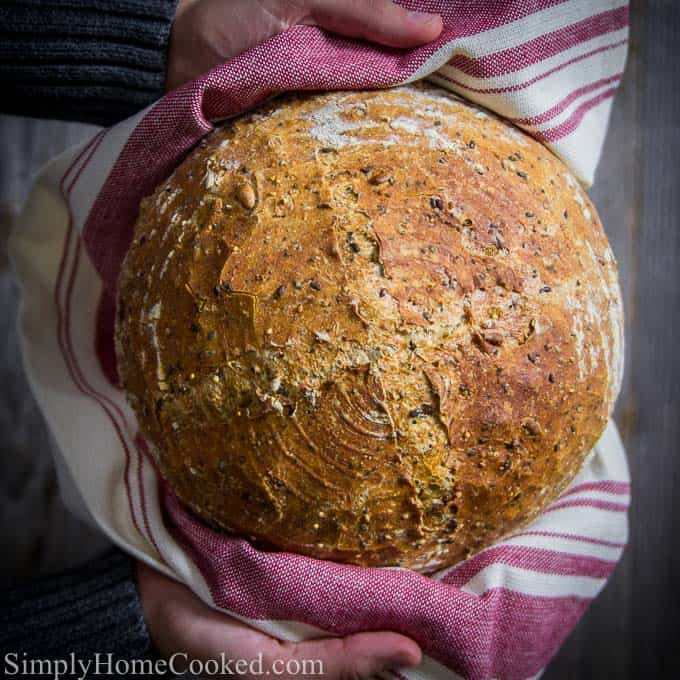 2 hands holding a Harvest Bread loaf using a burgundy and white towel.