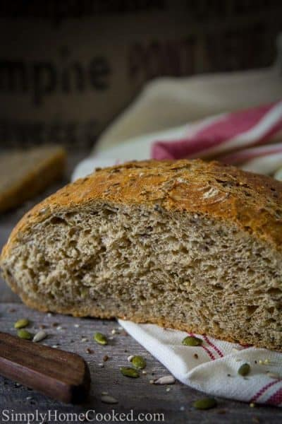 A loaf of Harvest Bread cut in half. Some seeds and grains around the harvest bread.
