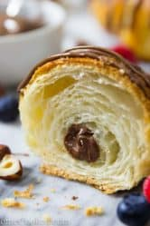a Nutella croissant cut open. raspberries, blueberries, and hazelnuts around the croissant.