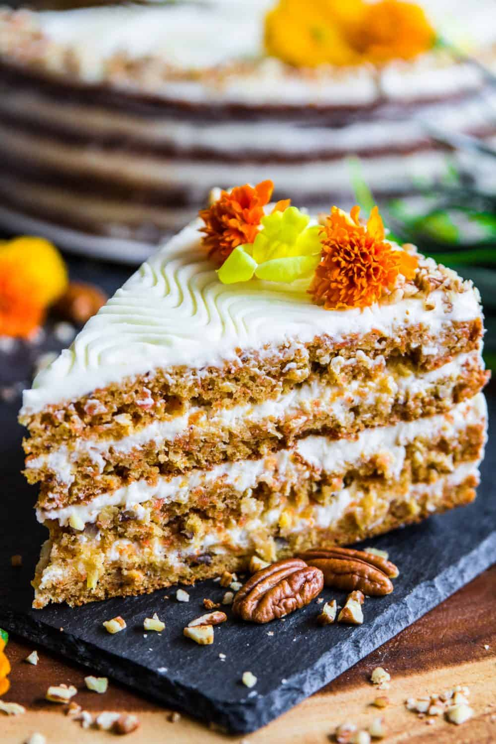 Slice of 4 layer carrot cake with flowers on top and pecans next to it, and a whole carrot cake in the background.