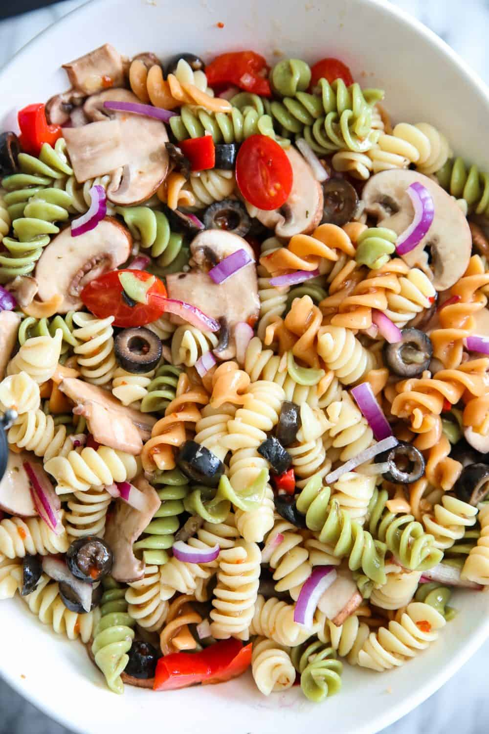 an overhead shot of a Tri Color Pasta Salad in a large white bowl. Its loaded with vegetables like mushroom, peppers, red onion, tomatoes, black olives.