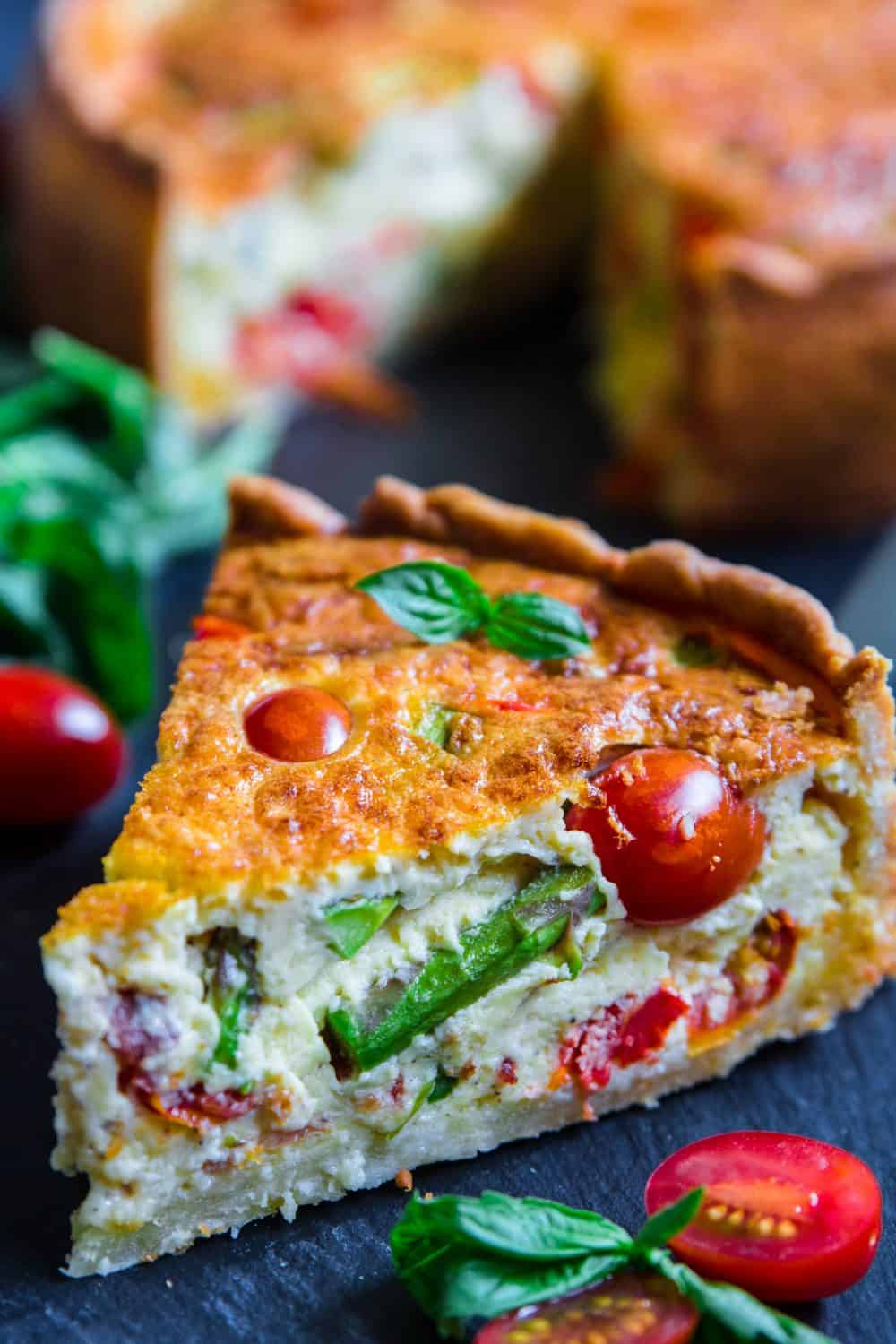 close up image of homemade quiche lorraine that is filled with spring vegetables like asparagus, tomatoes, and bacon