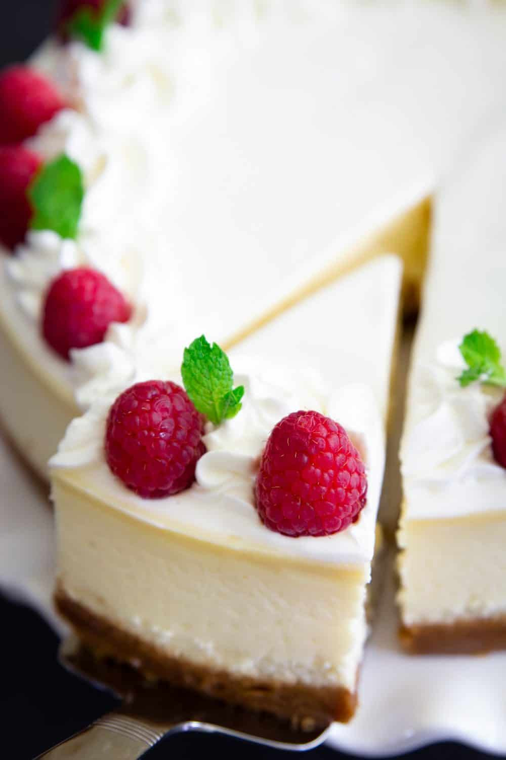 new york style cheesecake with raspberries and mint on top