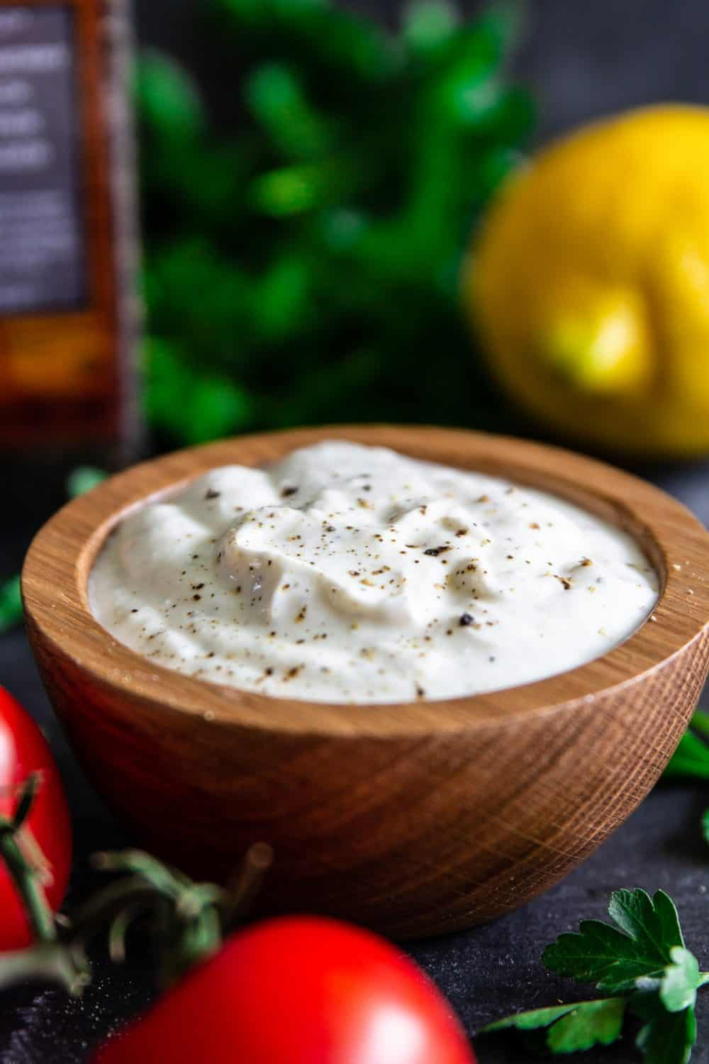 Creamy Greek Yogurt sauce with pepper sprinkled on top and a lemon in the background