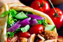 grilled chicken stuffed into pita bread with red onion, lettuce, and tomatoes on top