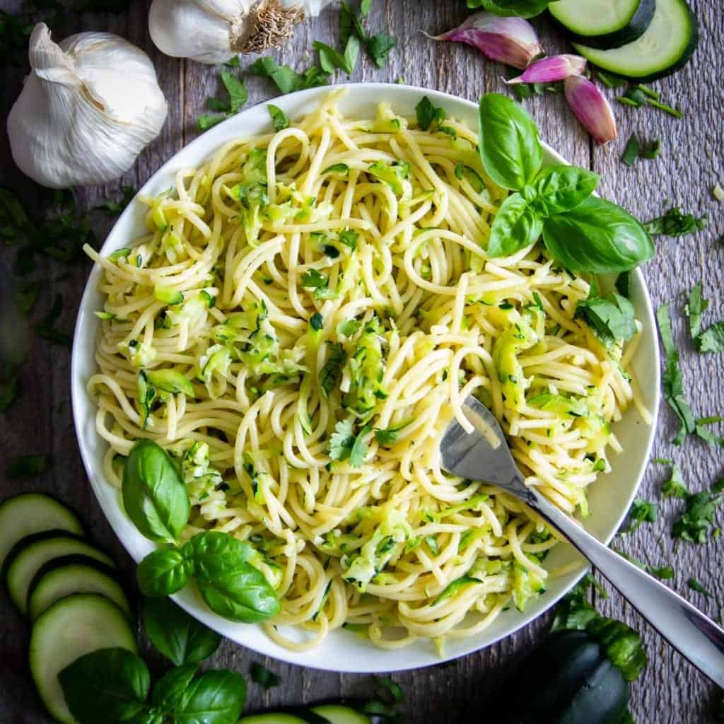 Pasta with zucchini in a white plate with a fork. some garlic cloves, zucchini, and shallots around the plate