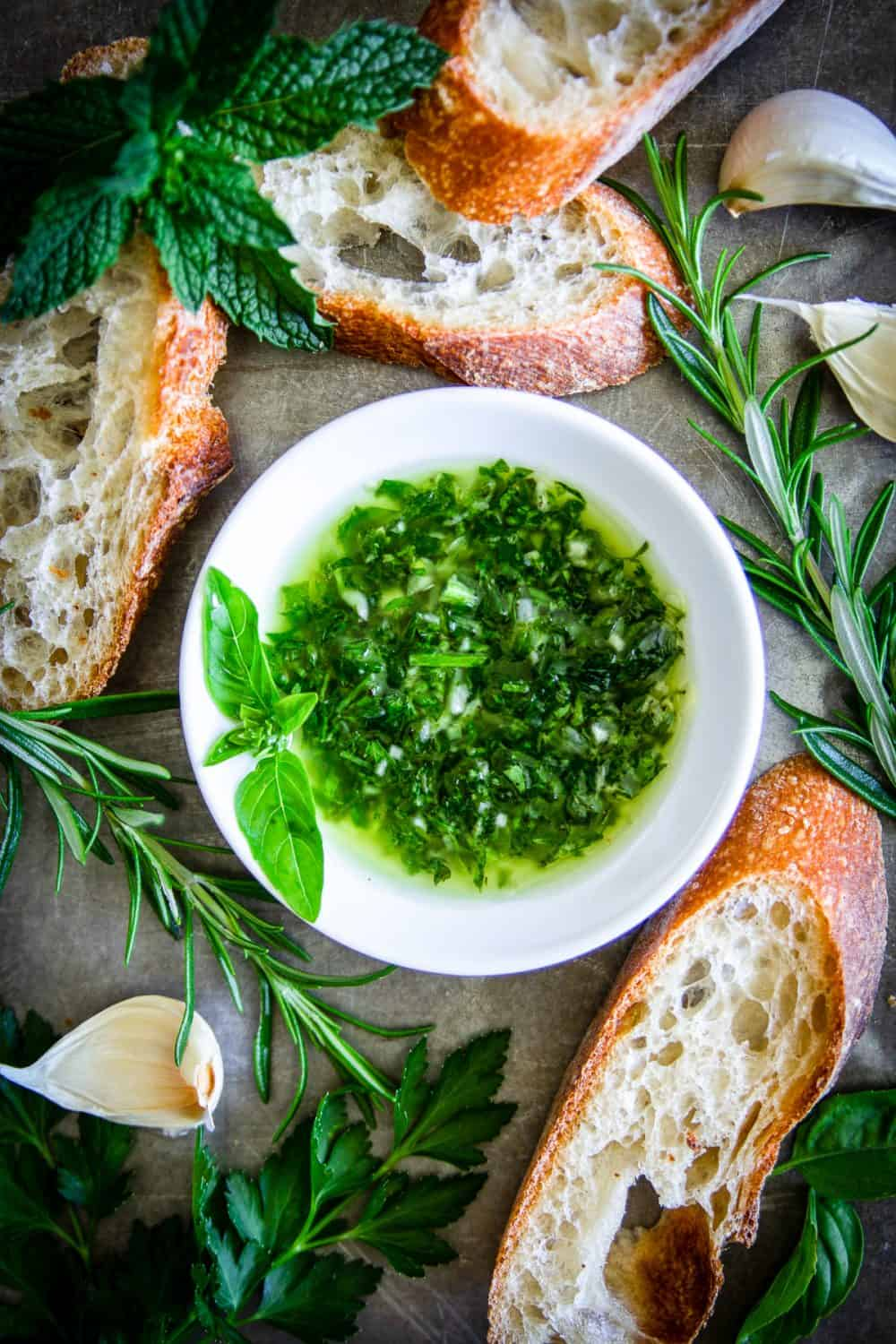 an overhead image of green herbed bread dipping oil with sliced crusty bread and rosemary beside it
