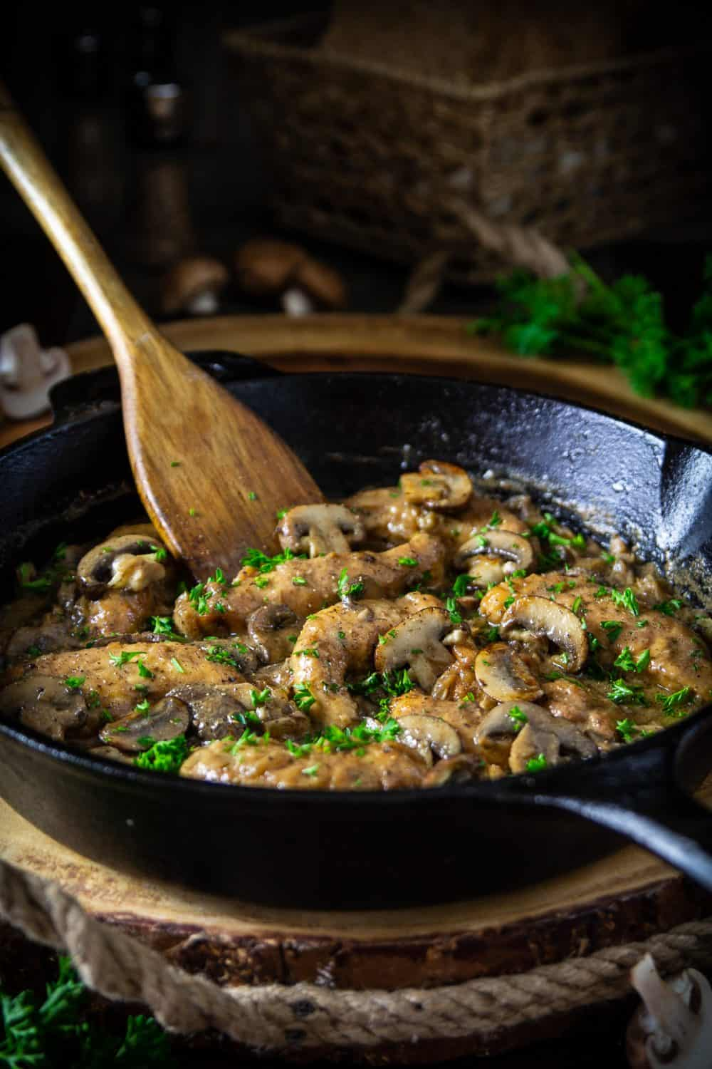 chicken marsala in a cast iron pan with a wooden spoon in the pan