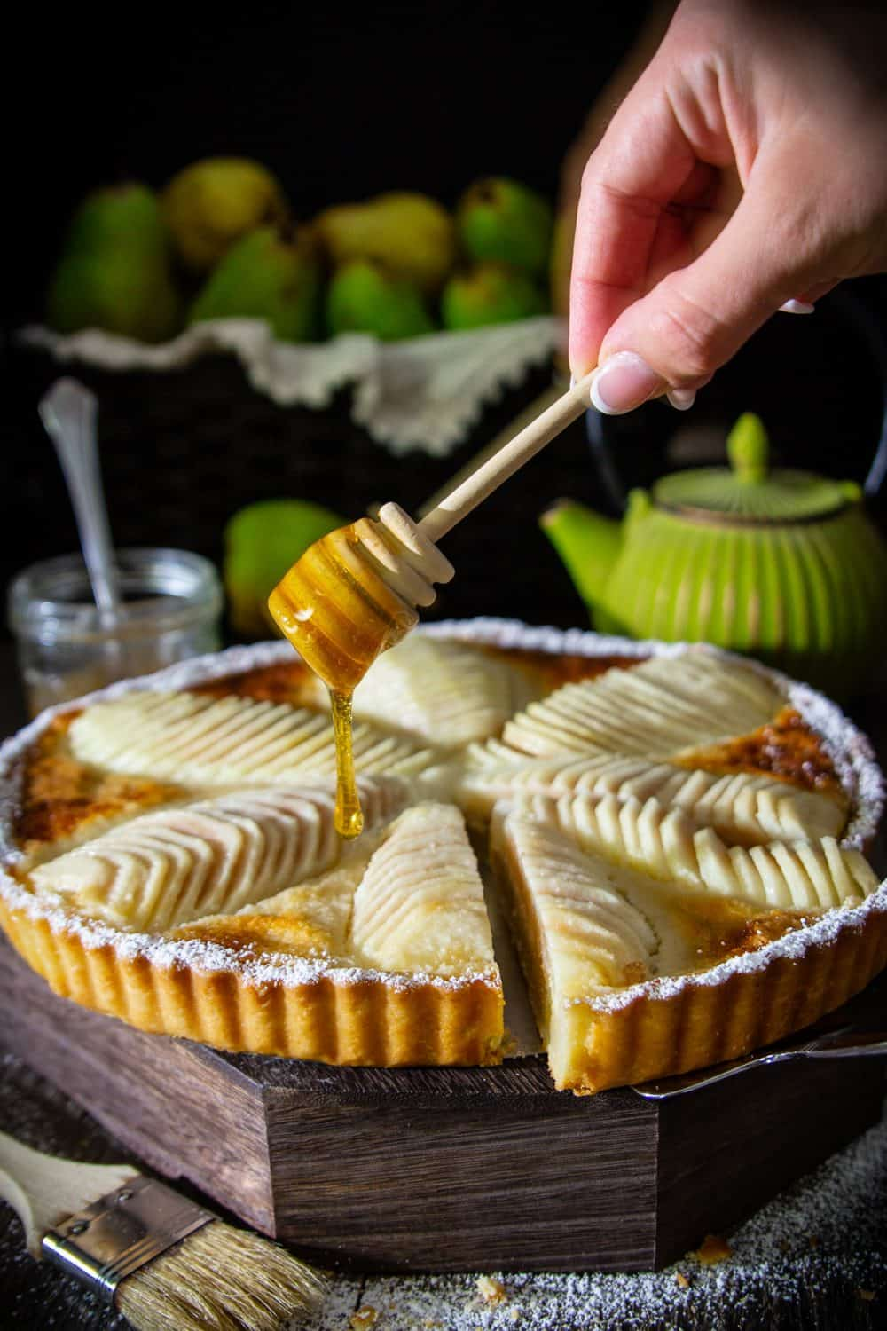 Pear tart sitting on a wooden surface with a hand shown drizzling fresh honey over the top of the tart and a green teapot and display of fresh pears in the background