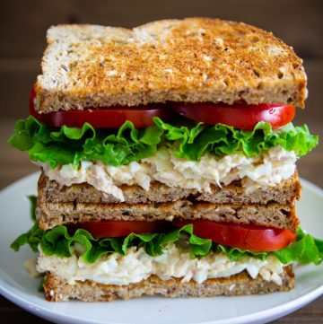 tuna salad sandwich on a white plate with lettuce, tomatoes, and whole wheat bread