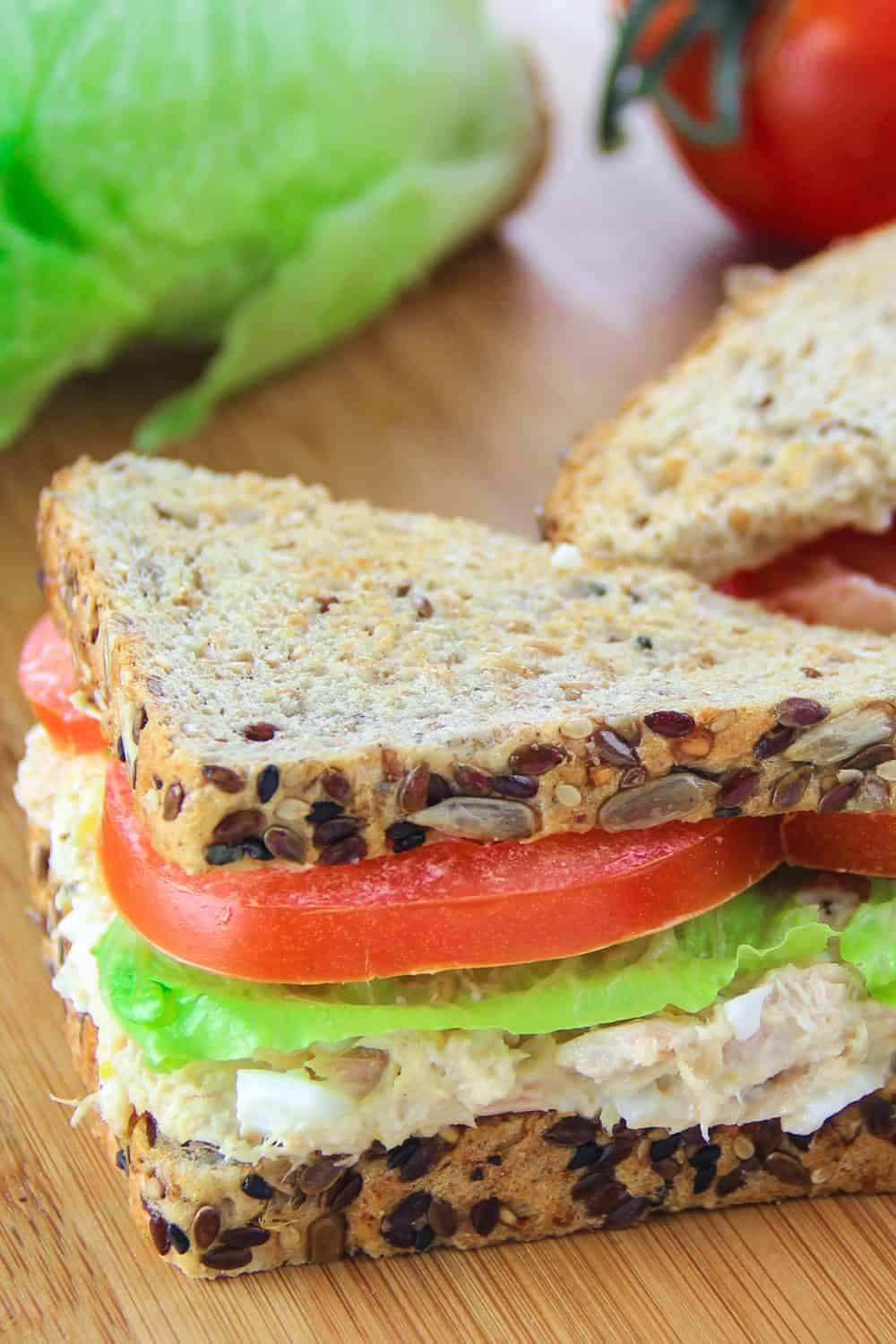 tuna salad sandwich on a wooden board with lettuce, tomatoes, and whole wheat bread