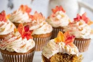 pumpkin spice cupcakes with cream cheese frosting and yellow-orange candy leaf topper