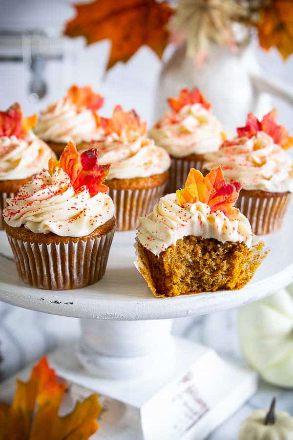 White platter on table with several pumpkin spice cupcakes that have been iced with white frosting and topped with decorative fall leaves with one up front with a bite out of it