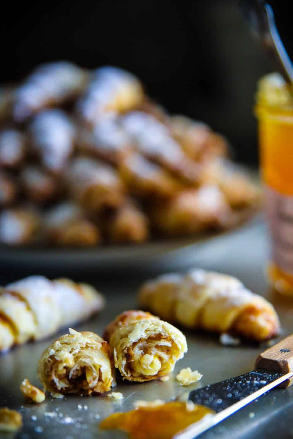 apricot walnut rugelach cookies sliced in half with apricot jam and a butter knife beside them