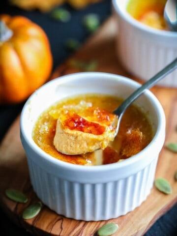 Pumpkin creme brulee with a spoon and pumpkin seeds around the ramekin