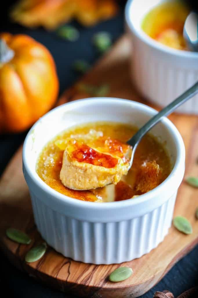 Pumpkin creme brulee with a spoon and pumpkin seeds around the ramekin