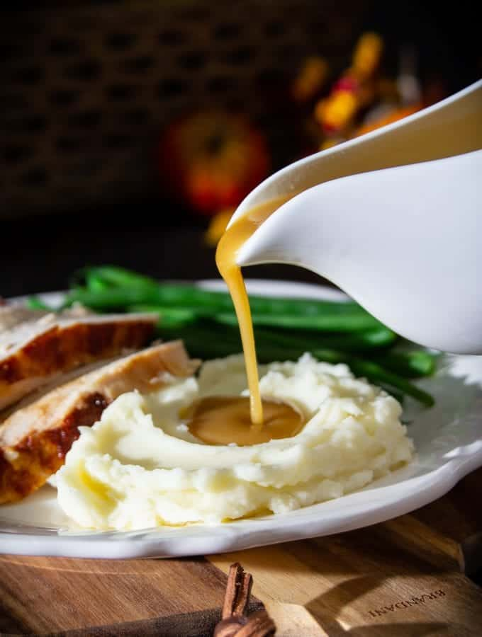 turkey gravy pouring into mashed potatoes with turkey breast and green beans on a plate