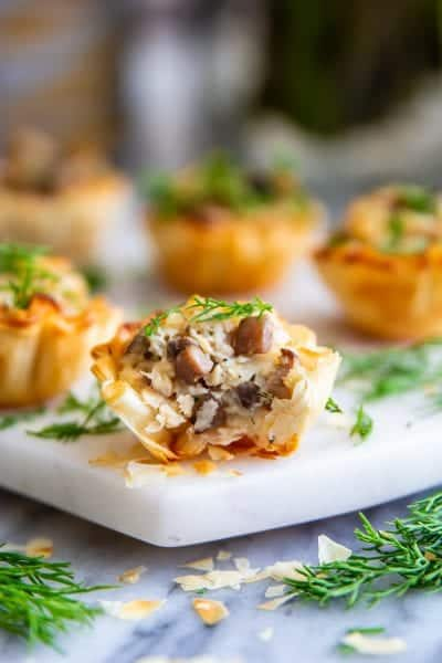 phyllo shells stuffed with chicken mushrooms and cheese and fresh dill on top